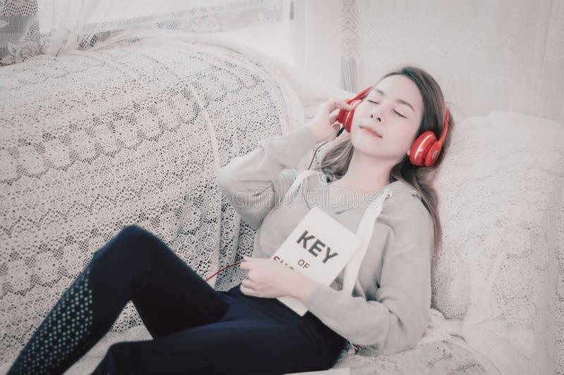 Härlig asiatisk kvinna som vilar och att lyssna till musik med röd hörlurar på soffan och en lycklig klubba i hem med avkoppling, arkivbild