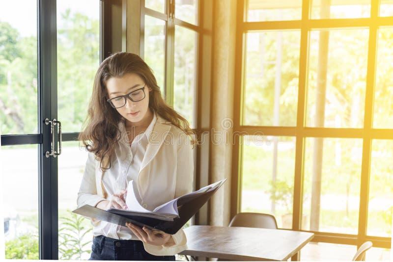 Härlig asiatisk kvinnablick på dokumentmappen E-kommers, universitetutbildning, internetteknologi eller startsmå och medelstora f royaltyfri bild