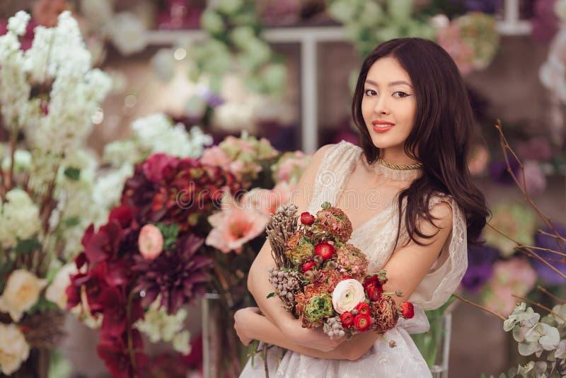 Härlig asiatisk kvinnablomsterhandlare i den vita klänningen med buketten av blommor i händer i blommalager royaltyfri bild