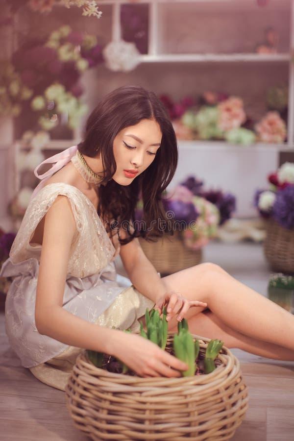 Härlig asiatisk kvinnablomsterhandlare i spets- vit klänning i blommalager royaltyfri fotografi