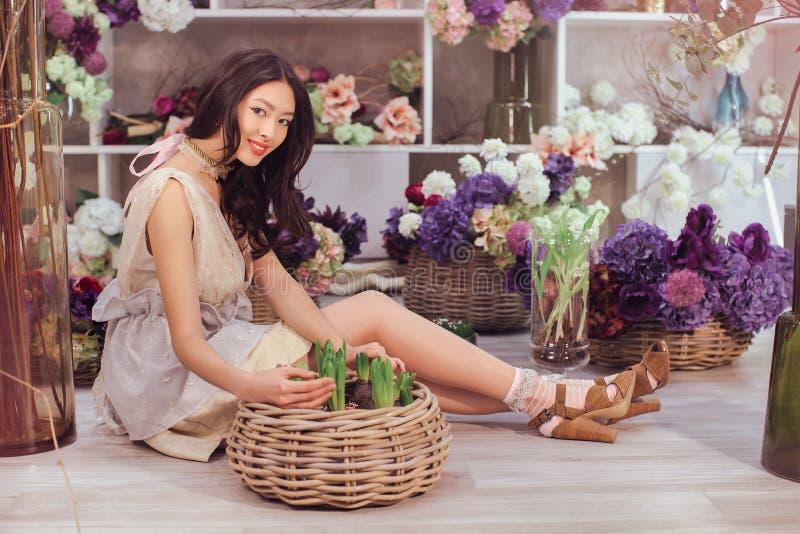 Härlig asiatisk kvinnablomsterhandlare i spets- vit klänning i blommalager arkivfoto