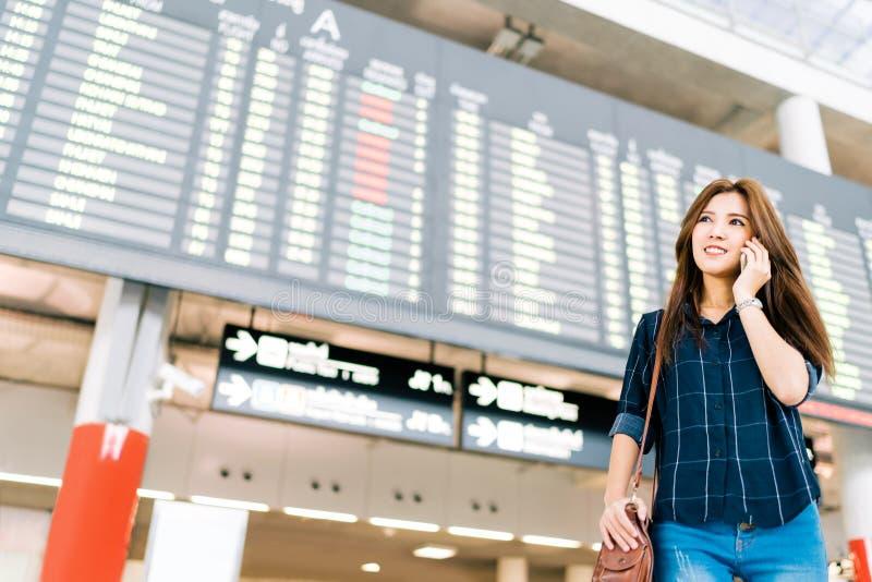 Härlig asiatisk kvinnahandelsresande på mobiltelefonappell på informationsbrädet om flyg i flygplats, begrepp för feriesemesterlo arkivbilder