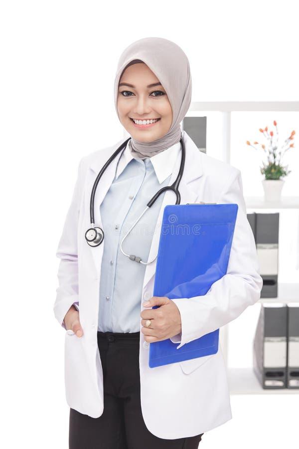 Härlig asiatisk kvinnlig doktor med stetoskopet och blocket royaltyfria foton
