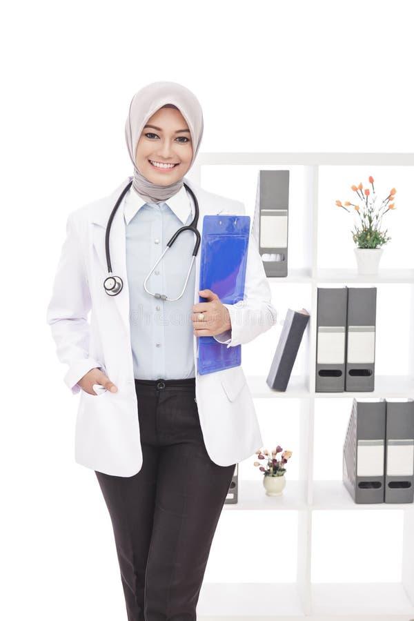 Härlig asiatisk kvinnlig doktor med stetoskopet och blocket arkivfoton