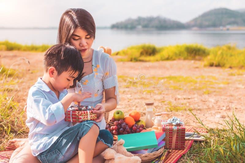 Härlig asiatisk moder och son som gör picknicken och öppnar gåvaasken från överraskning i födelsedagparti på äng nära sjön och be arkivbild