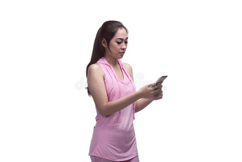 Härlig asiatisk sportig kvinna som använder mobiltelefonen för messaging royaltyfri bild