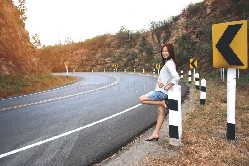 Härlig asiatisk ställning för ung kvinna nära vägen och den lyckliga känslan arkivfoto