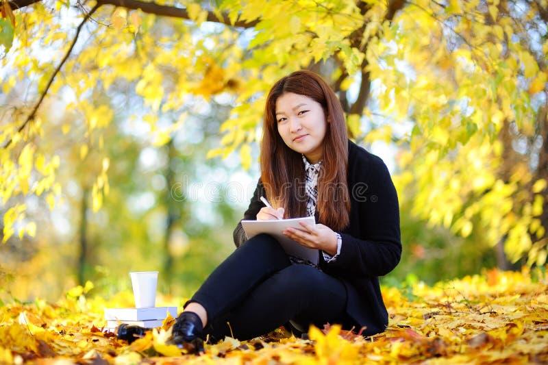Härlig asiatisk stående för studentflicka utomhus arkivfoto