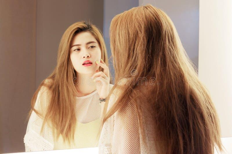 Härlig asiatisk tonårs- flicka som trycker på hennes framsida för spegeln royaltyfria bilder