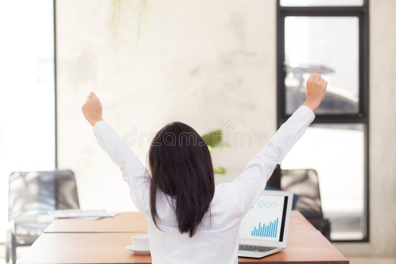 Härlig asiatisk ung affärskvinna som är upphetsad och som är glad av framgång med bärbara datorn royaltyfri foto