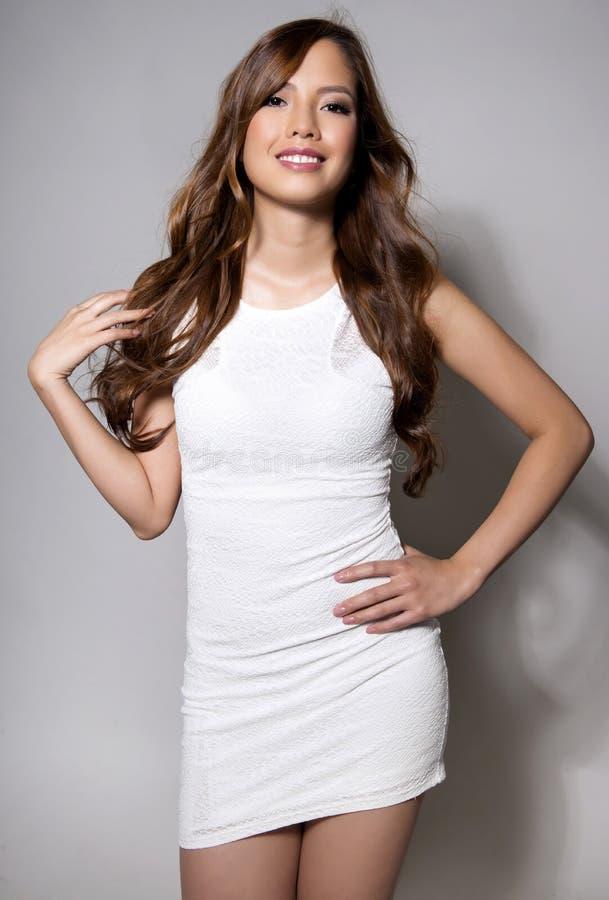 Härlig asiatisk ung kvinna i den vita klänningen med prickfri hud royaltyfria bilder