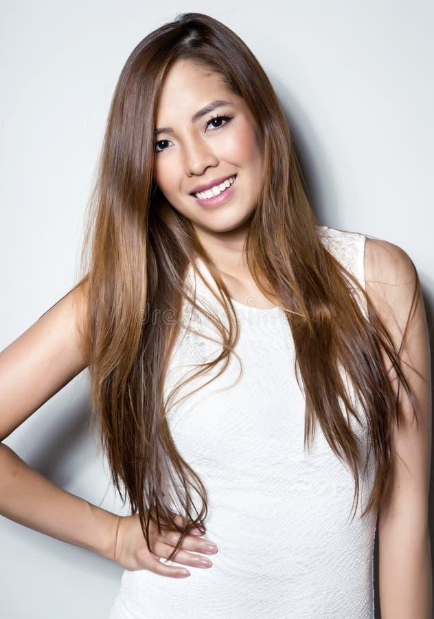 Härlig asiatisk ung kvinna i den vita klänningen med prickfri hud royaltyfria foton