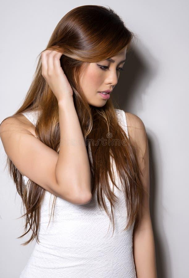 Härlig asiatisk ung kvinna i den vita klänningen med prickfri hud arkivbild