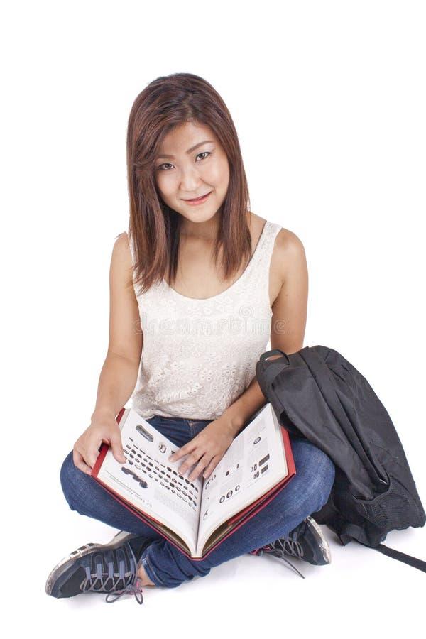 Härlig asiatisk ung kvinna med ryggsäcken som läser den röda boken arkivbilder