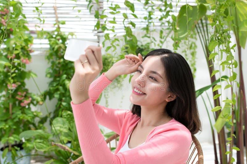 Härlig asiatisk ung kvinna som hemma kopplar av och använder mobiltelefonen på balkong arkivfoton