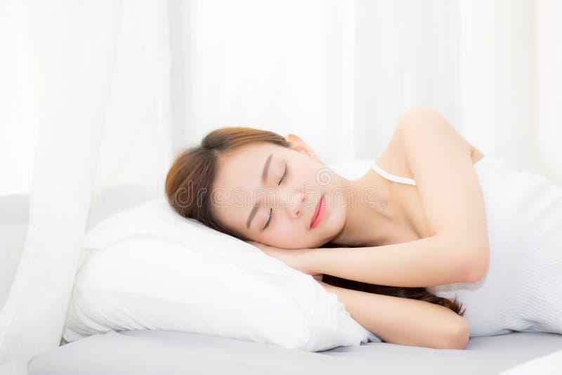 Härlig asiatisk ung kvinna som sover att ligga i säng med huvudet på den lycklig kudden som är bekväm och royaltyfria foton