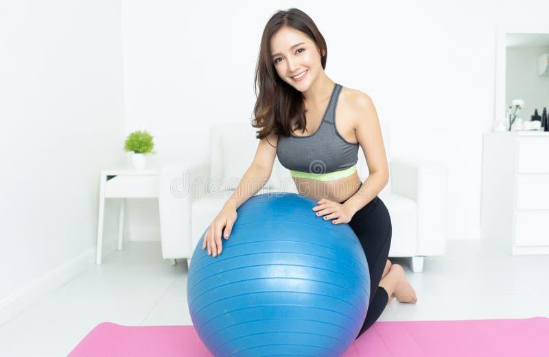 Härlig asiatisk ung sportig kvinna för stående som utarbetar med den gymnastiska blåa färdiga bollen och ser kameran i hem Sport  royaltyfria bilder