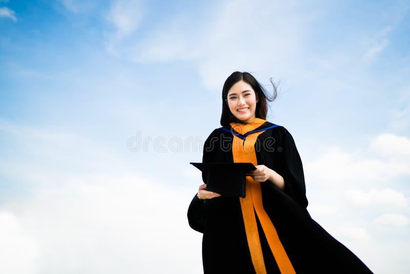 Härlig asiatisk universitet- eller högskoladoktorandkvinna som ler i den akademiska klänningen för avläggande av examen eller kap arkivfoto