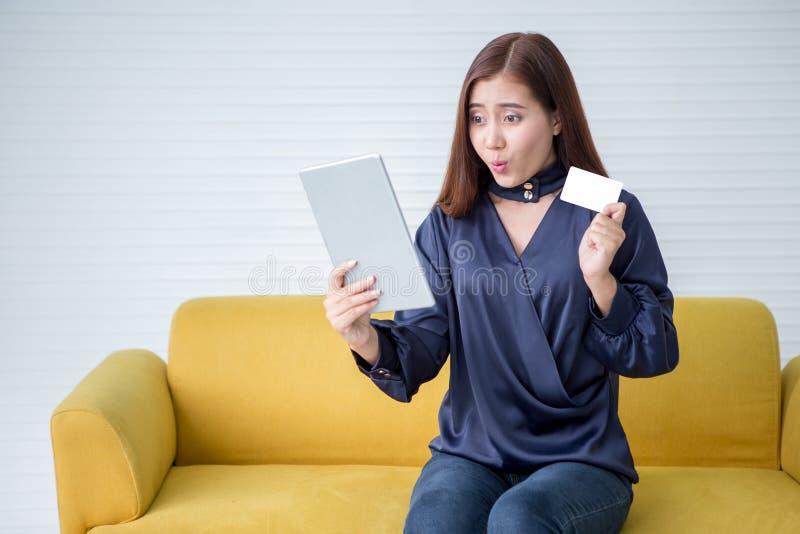 Härlig asiatisk visningkreditkort för ung kvinna som rymmer den digitala minnestavladatoren som direktanslutet shoppar dundersucc arkivbilder
