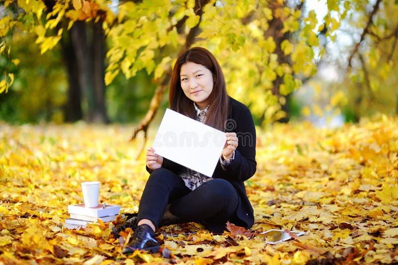 Härlig asiatisk whiteboard för studentinnehavmellanrum i henne händer arkivbilder