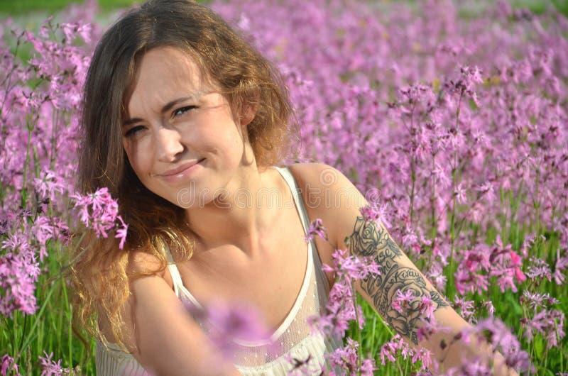Härlig attraktiv ung flicka på ursnygg äng mycket av lösa blommor royaltyfri bild