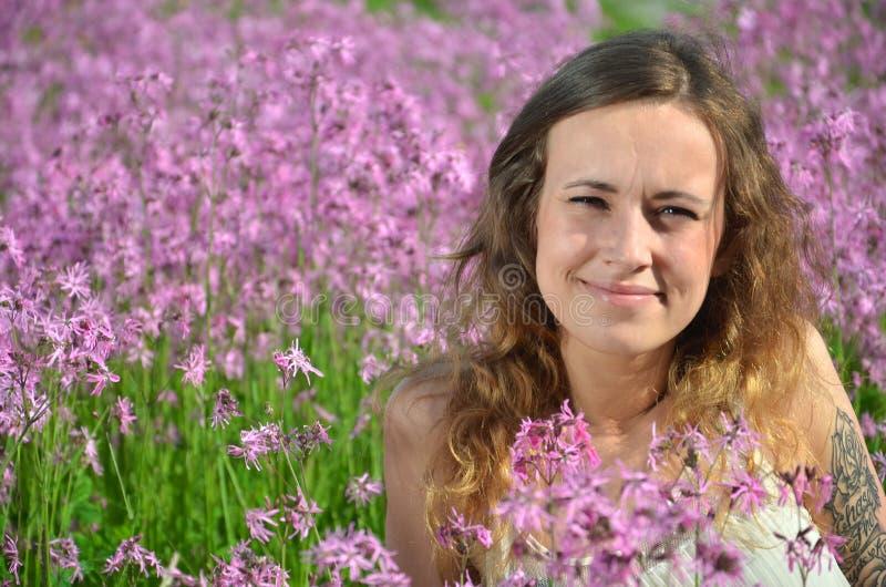 Härlig attraktiv ung flicka på ursnygg äng mycket av lösa blommor arkivfoton