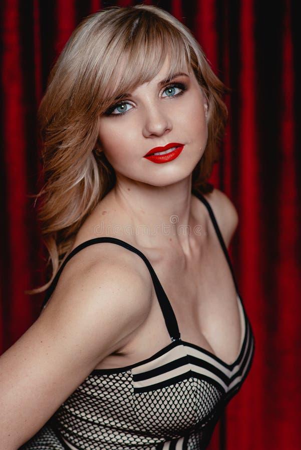 Härlig attraktiv ung kvinna med smink i den stilfulla klänningen som stending nära den röda sammetgardinen i aftonen royaltyfria foton