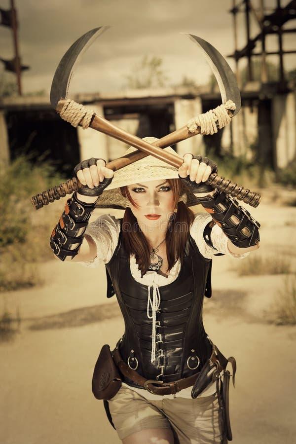 Härlig attrctive aggressiv kvinnlig krigare som rymmer två svärd royaltyfri foto