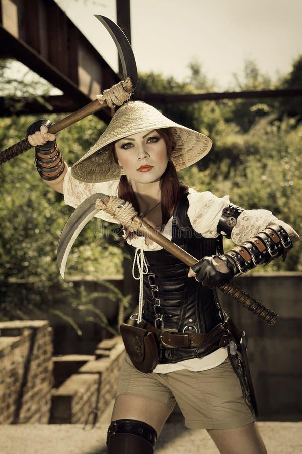 Härlig attrctive kvinnlig krigare som rymmer två svärd och fighti royaltyfri bild