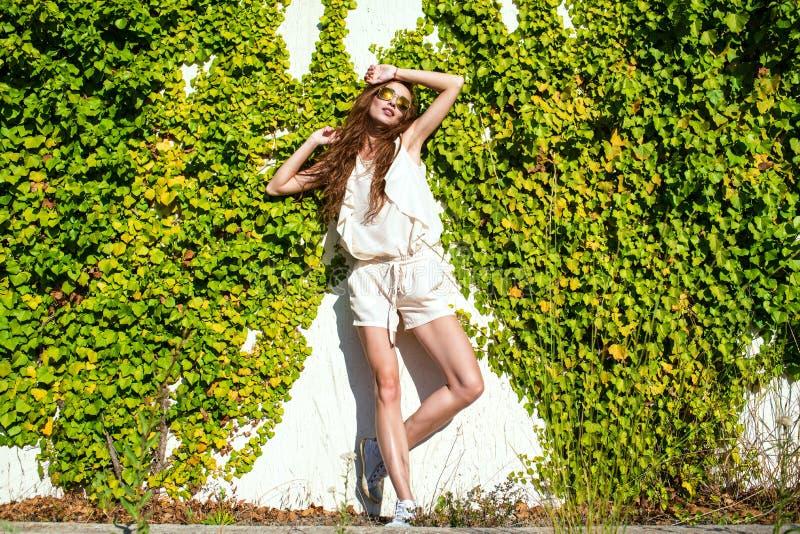 Härlig avkopplad kvinna med långt kastanjebrunt håranseende på väggen som tvinnas med murgrönan som tycker om solskenet arkivfoto
