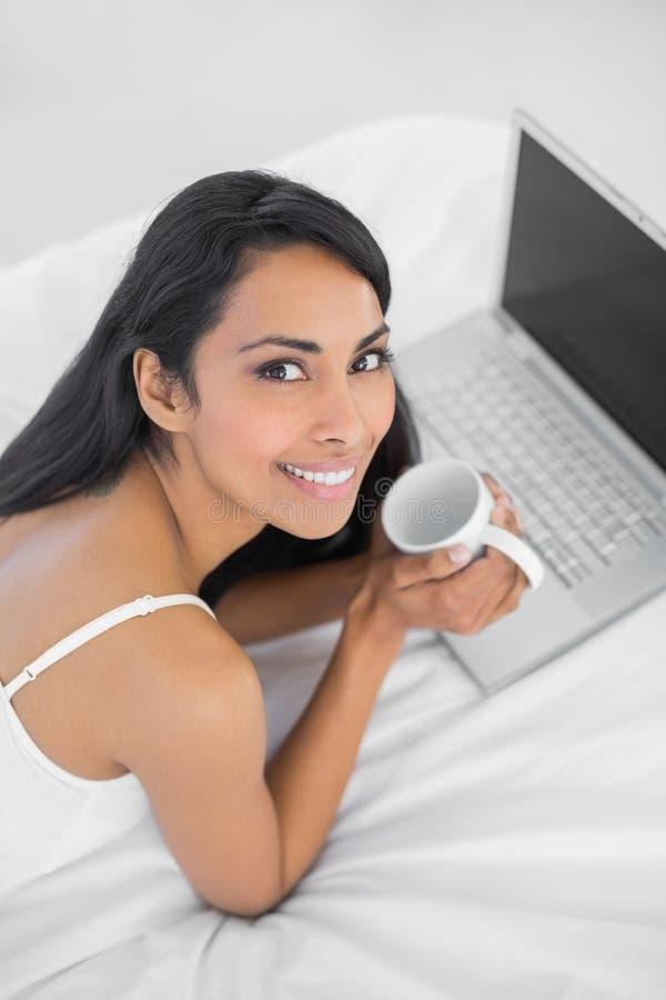 Härlig avslappnande kvinna som rymmer en kopp som ligger på säng royaltyfri fotografi