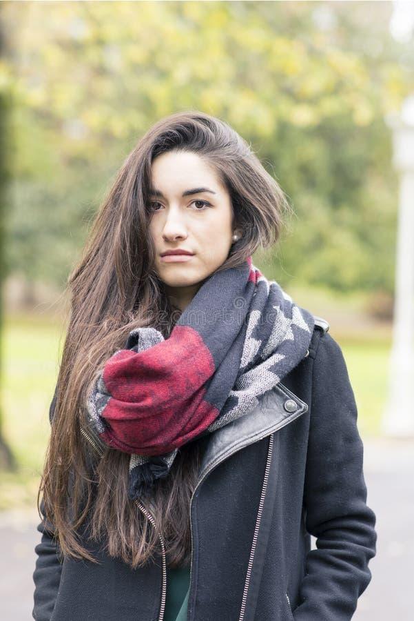 Härlig bärande halsduk för ung kvinna i parkera royaltyfri foto