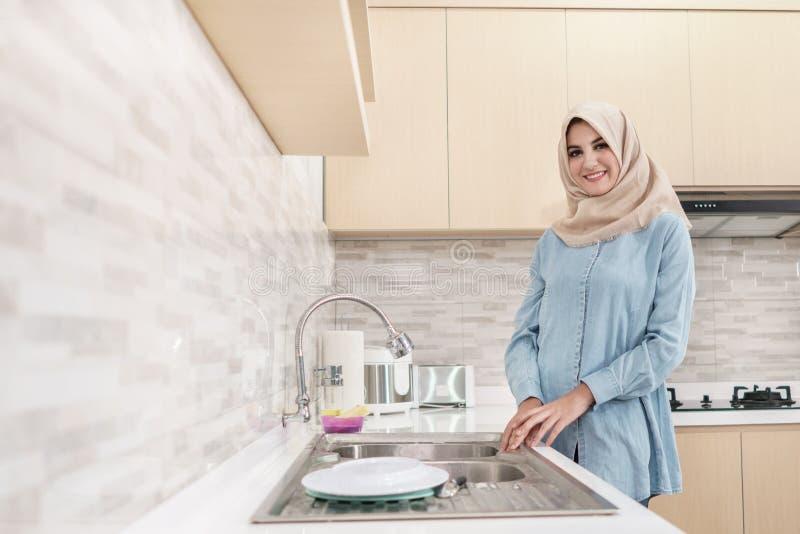 Härlig bärande hijab för ung kvinna som tvättar disken arkivbilder