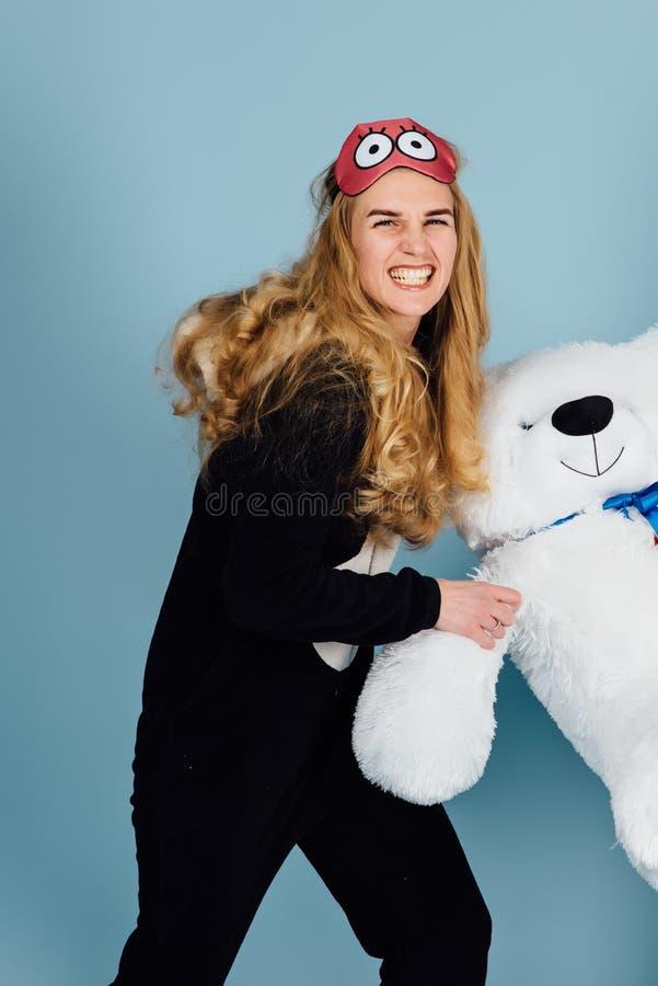 Härlig bärande pyjamas för en ung kvinna som kramar hennes välfyllda nallebjörn royaltyfria bilder