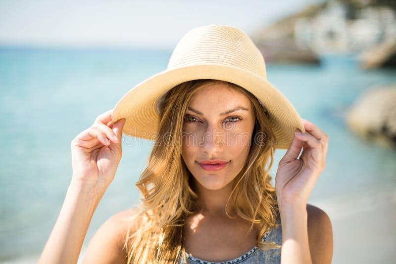 Härlig bärande solhatt för ung kvinna arkivfoto