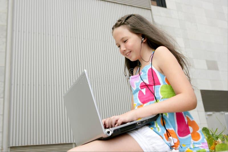 härlig bärbar dator för brunettstadsflicka little som är teen arkivfoto