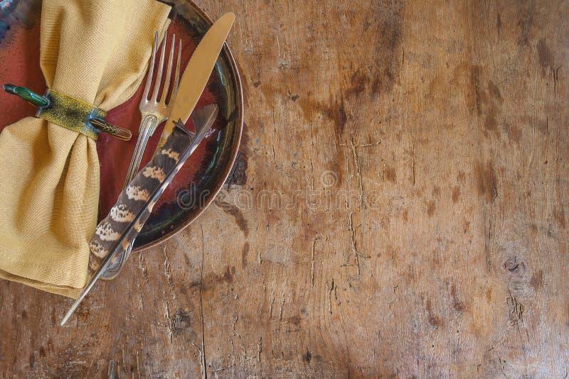 Härlig bakgrund, i att jaga stil: servett-, bestick- och fasanfjäder på den lantliga träbakgrunden med kopieringsutrymme royaltyfri fotografi