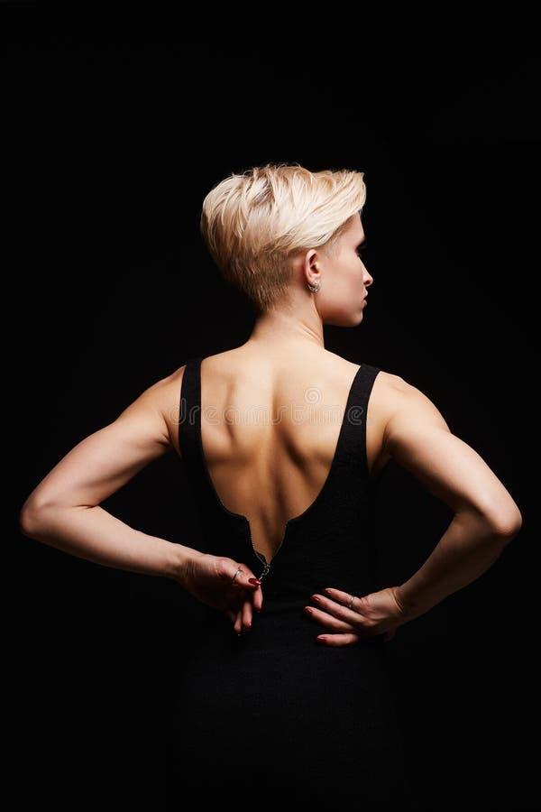 Härlig baksida av den unga kvinnan i en svart sexig klänning royaltyfri foto