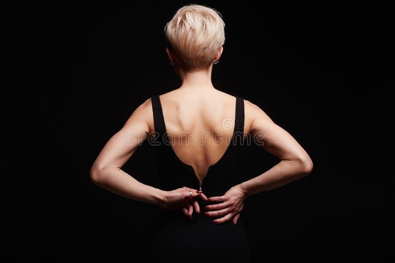 Härlig baksida av den unga kvinnan i en svart sexig klänning arkivfoto