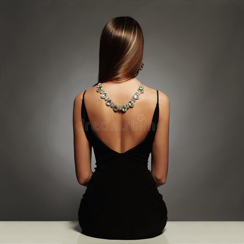 Härlig baksida av den unga kvinnan i en svart sexig klänning lyx flicka för flicka för skönhetbrunettsammanträde med en halsband  arkivfoto