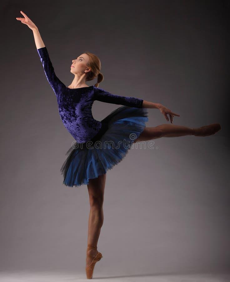 Härlig ballerina med den perfekta kroppen i blå ballerinakjoldräktdans i studio Balettkonst arkivbild