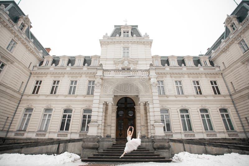 Härlig ballerina som hoppar bredvid byggnad på snöbakgrund arkivfoto