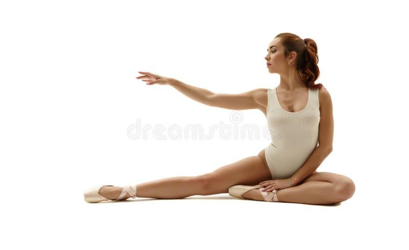 Härlig ballerina som poserar att sitta behagfullt royaltyfri foto