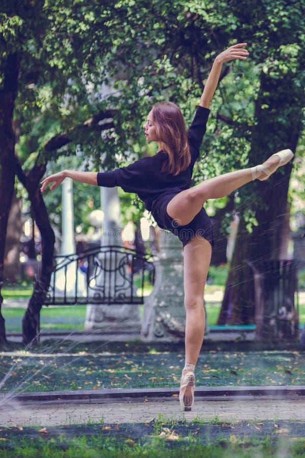 Härlig ballerinaflicka i tillfällig kläder som poserar på en suddig bakgrund av parkeraträden på bakgrund royaltyfria bilder
