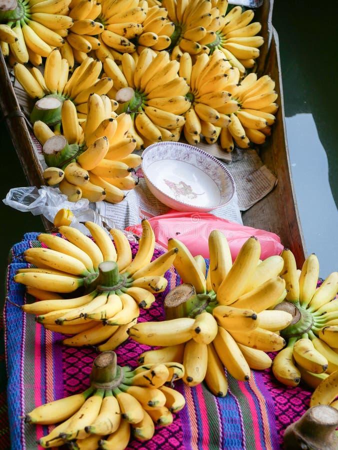 Härlig banangrupp i traditionellt litet träfartyg, i att sväva marknaden i Damnoen Saduak, Thailand arkivfoto