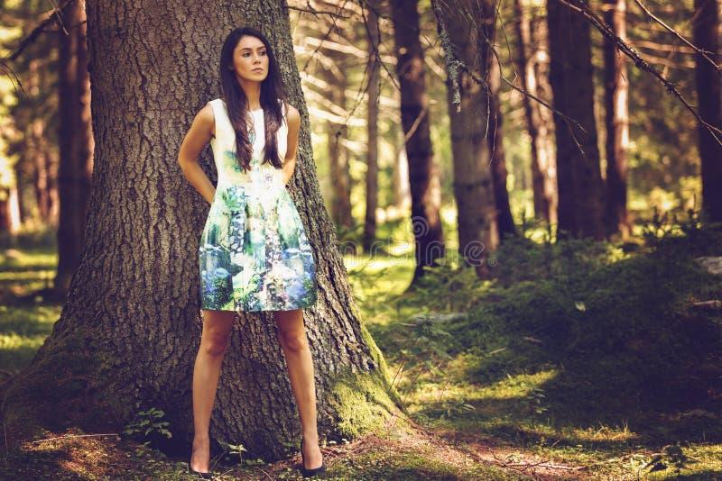 Härlig barnmodekvinna, i att posera för färgklänning som är utomhus- i G arkivfoton