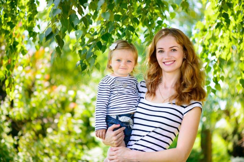 Härlig barnmoder och gullig dotter som ler på naturen arkivfoton