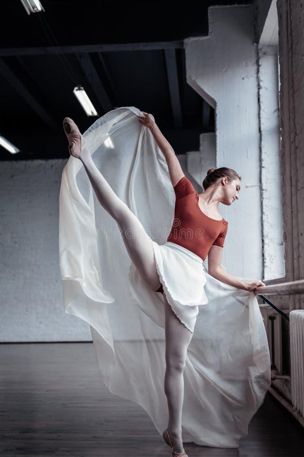 Härlig begåvad ballerina som rymmer upp hennes ben fotografering för bildbyråer
