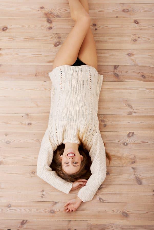 Härlig bekymmerslös ung tillfällig kvinna som ligger på golvet. arkivfoto