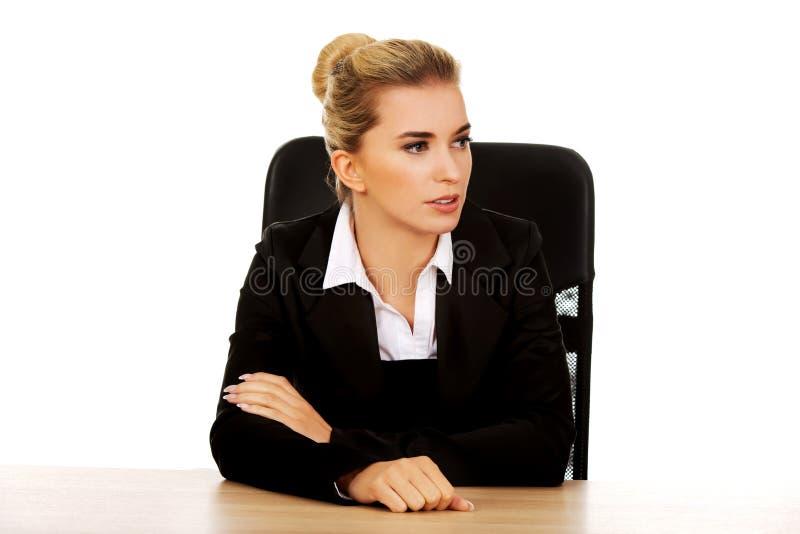 Härlig bekymrad affärskvinna bak skrivbordet arkivbild